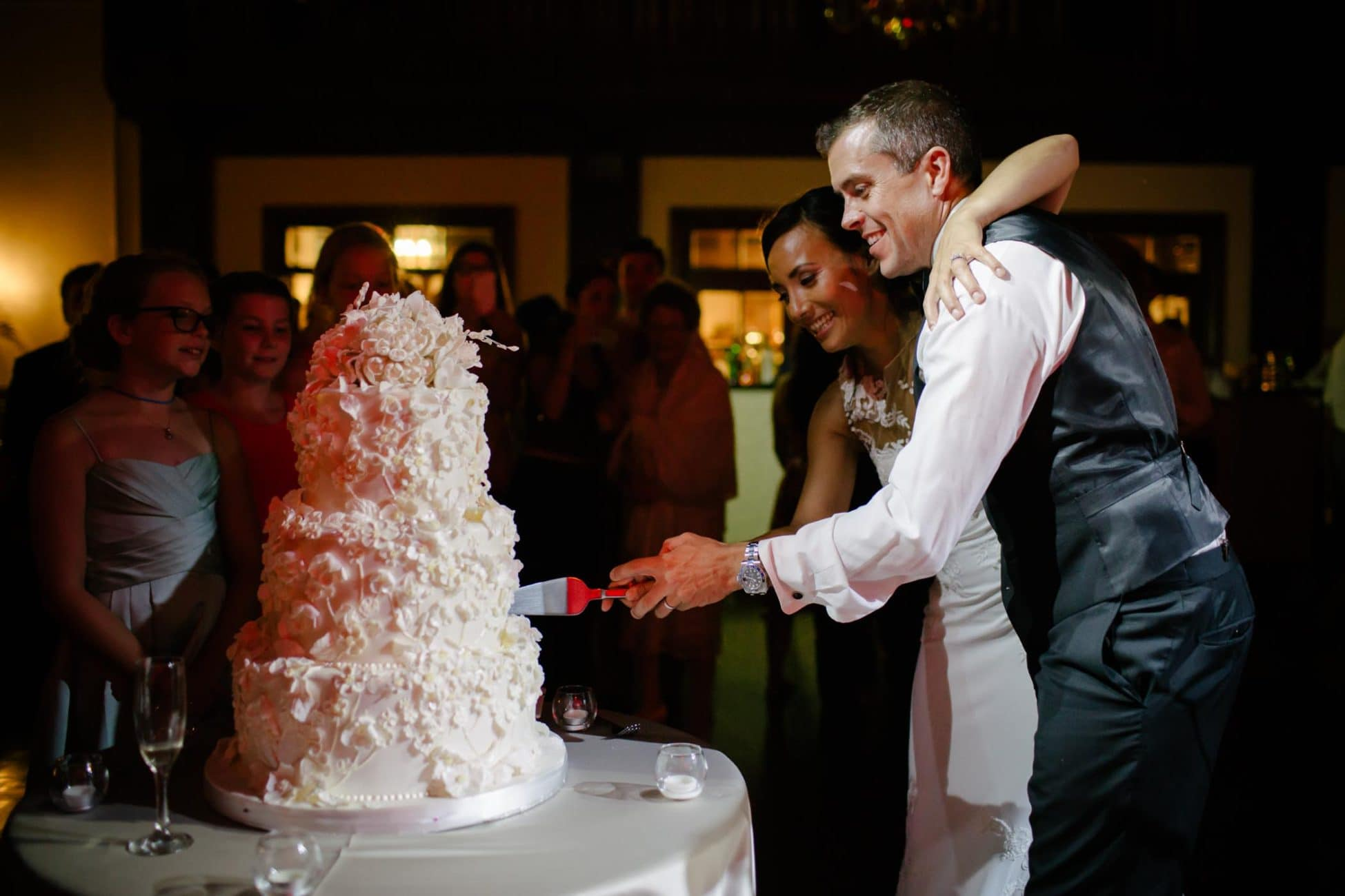 Bride and groom cutting wedding cake. Bride has hand over groom's shoulder and they are standing in centre of bright light with guests in darkness behind them. Reception area of The Boulevard Club. By Toronto Wedding Photographer Pavel Kounine.