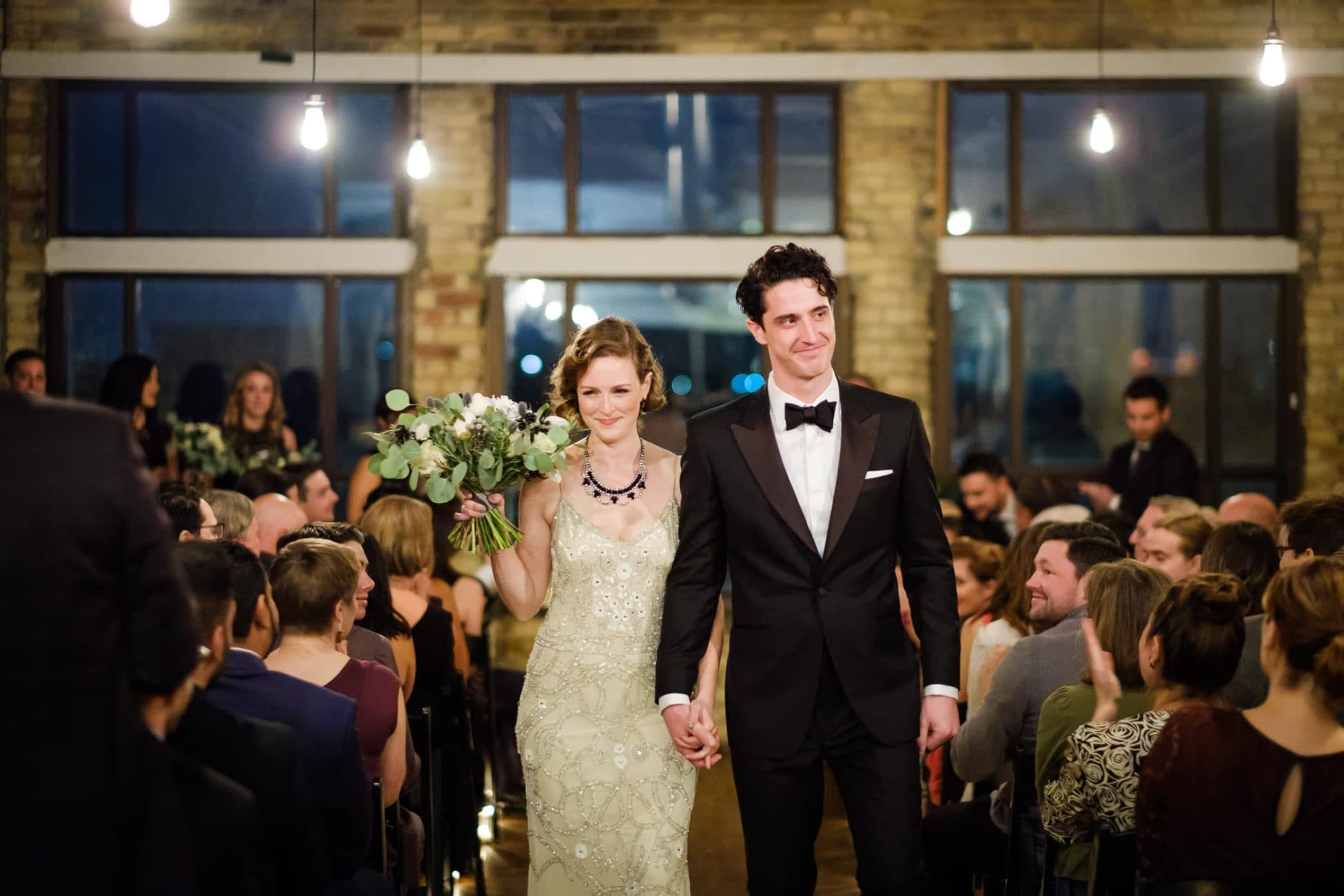 After getting married, the bride and groom walk down aisle at The Burroughes Building.
