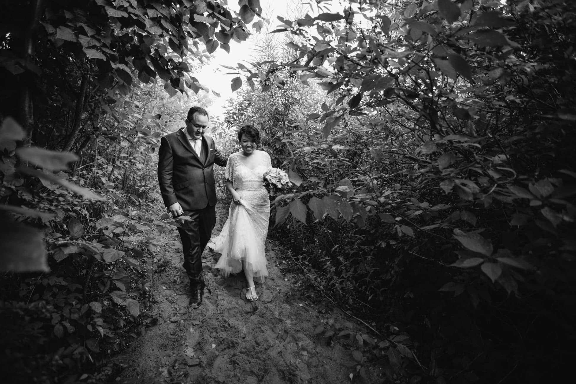 The bride and groom walk down a sandy path surrounded by bushes towards their Artscape on Toronto Island wedding reception.