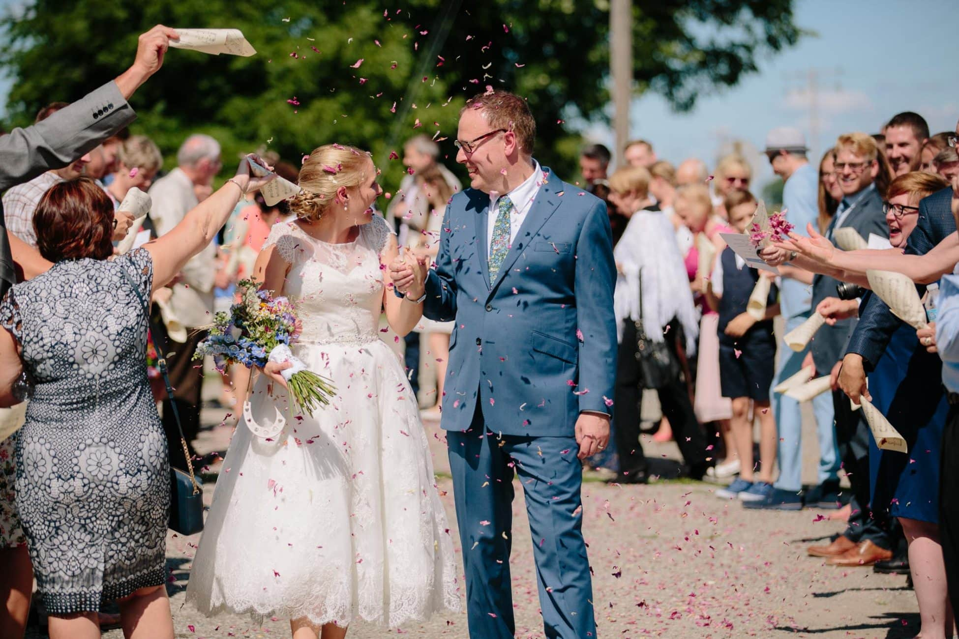 The bride and groom are showered with flower petals by guests outside a countryside church.