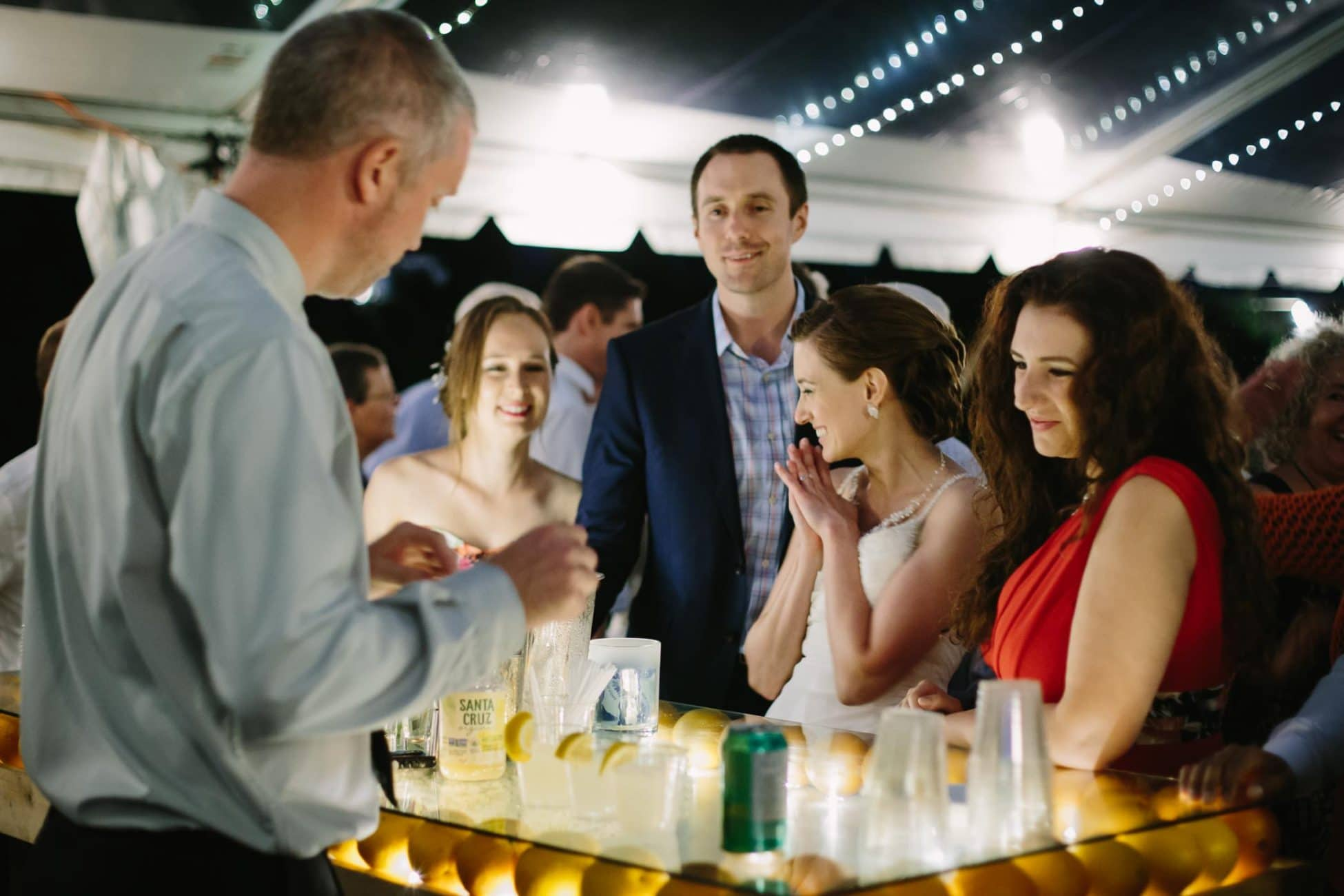 The bride smiles with hands brought together while ordering a beverage with her friends at a mobile bar whose glass surface is supported by dozens of lemons and oranges.