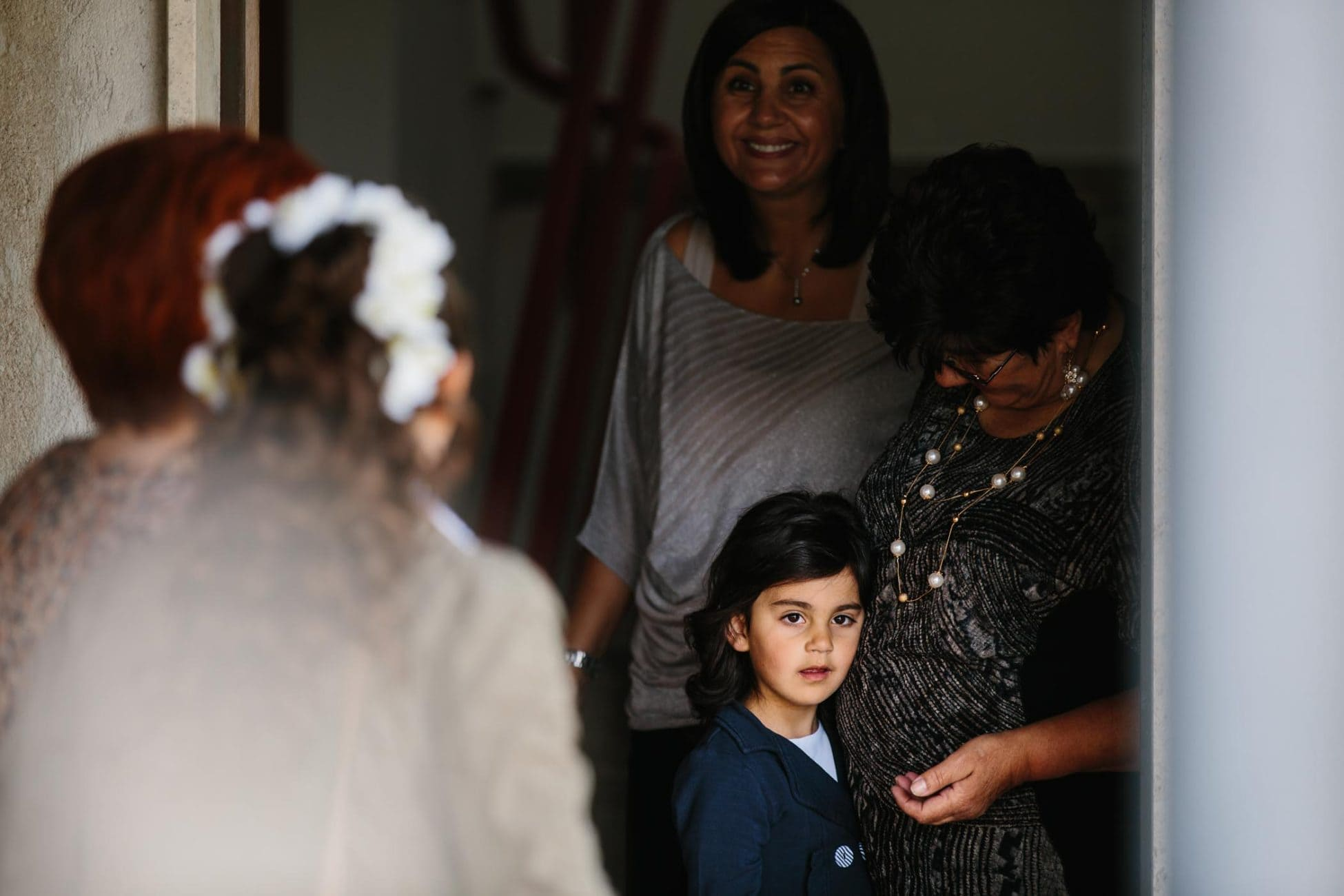 A little girl leans on an older woman's stomach in doorway with bride in foreground.