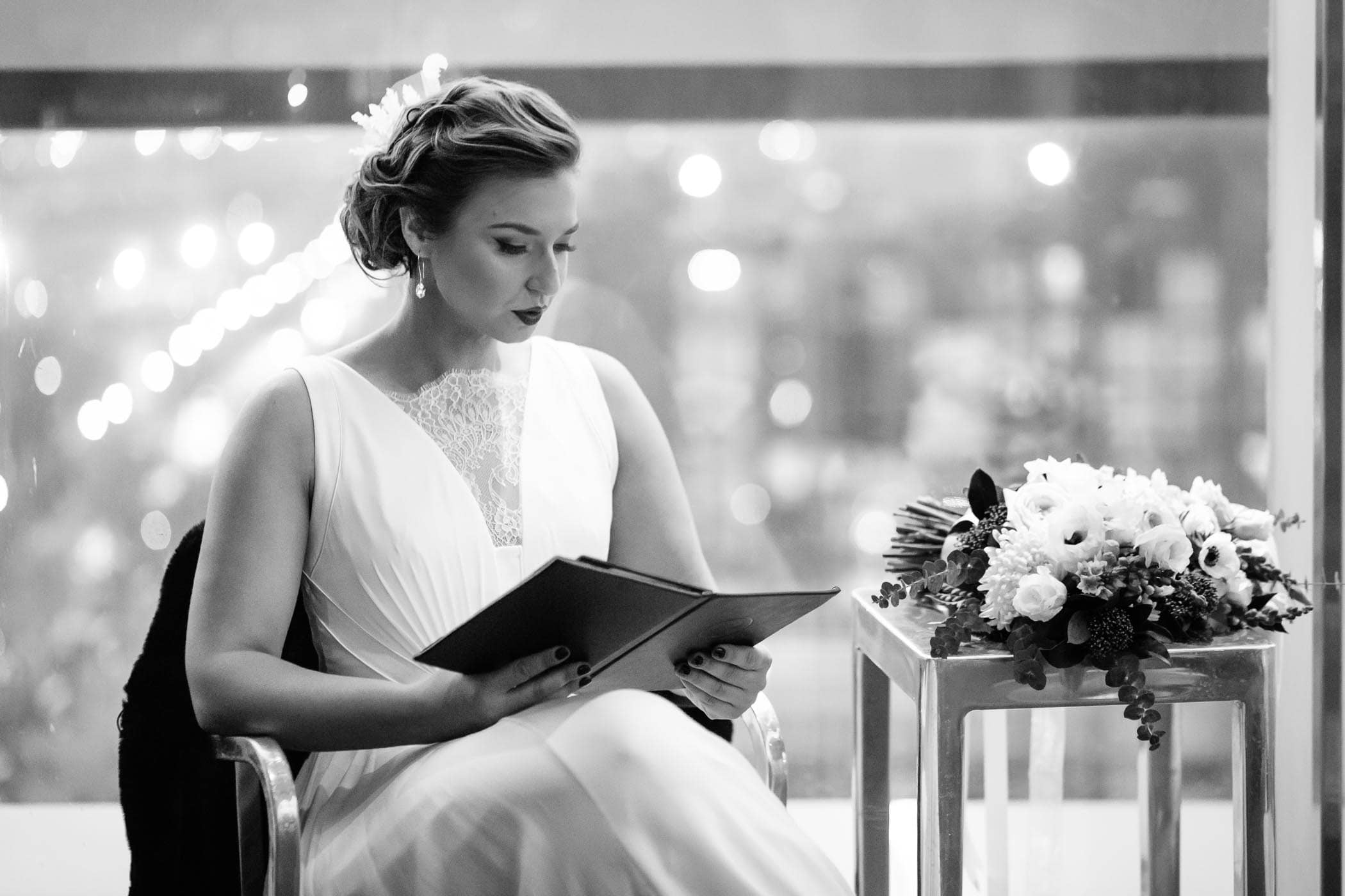 The bride sitting in front of large window reading menu in rooftop bar of Thompson Hotel in Toronto