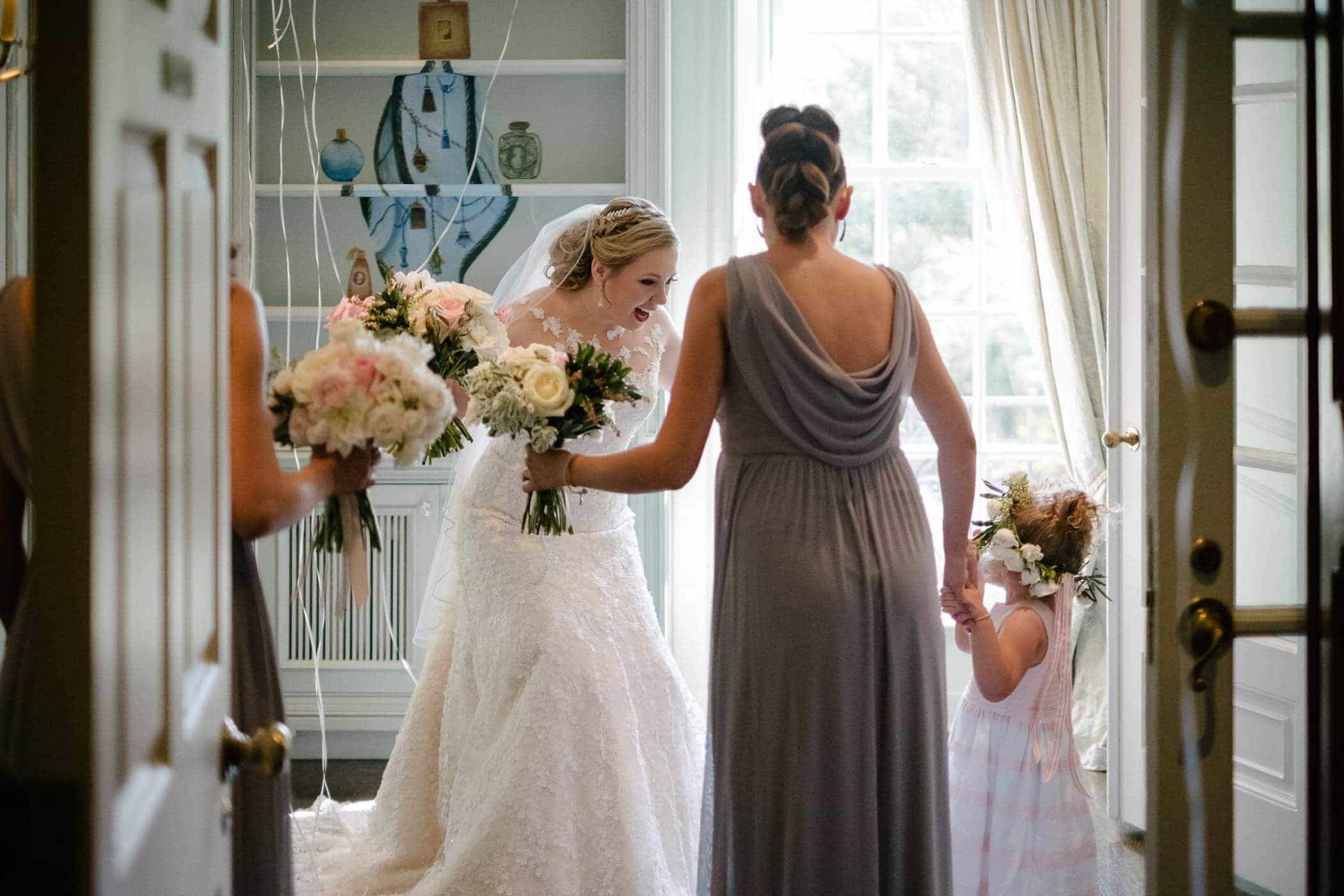 The bride holding flowers smiles enthusiastically at flower girl inside The McLean House at Estates of Sunnybrook wedding. Image by Toronto wedding photographer Pavel Kounine.