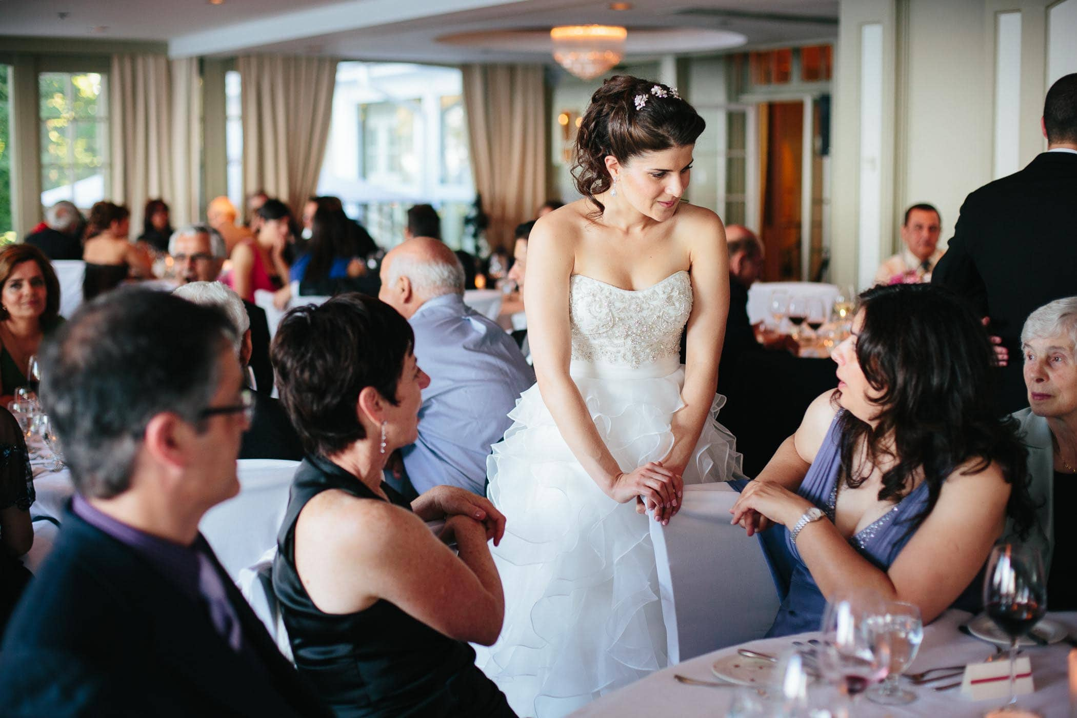 The bride leans on chair back talking to guests at The Toronto Hunt club wedding reception hall.