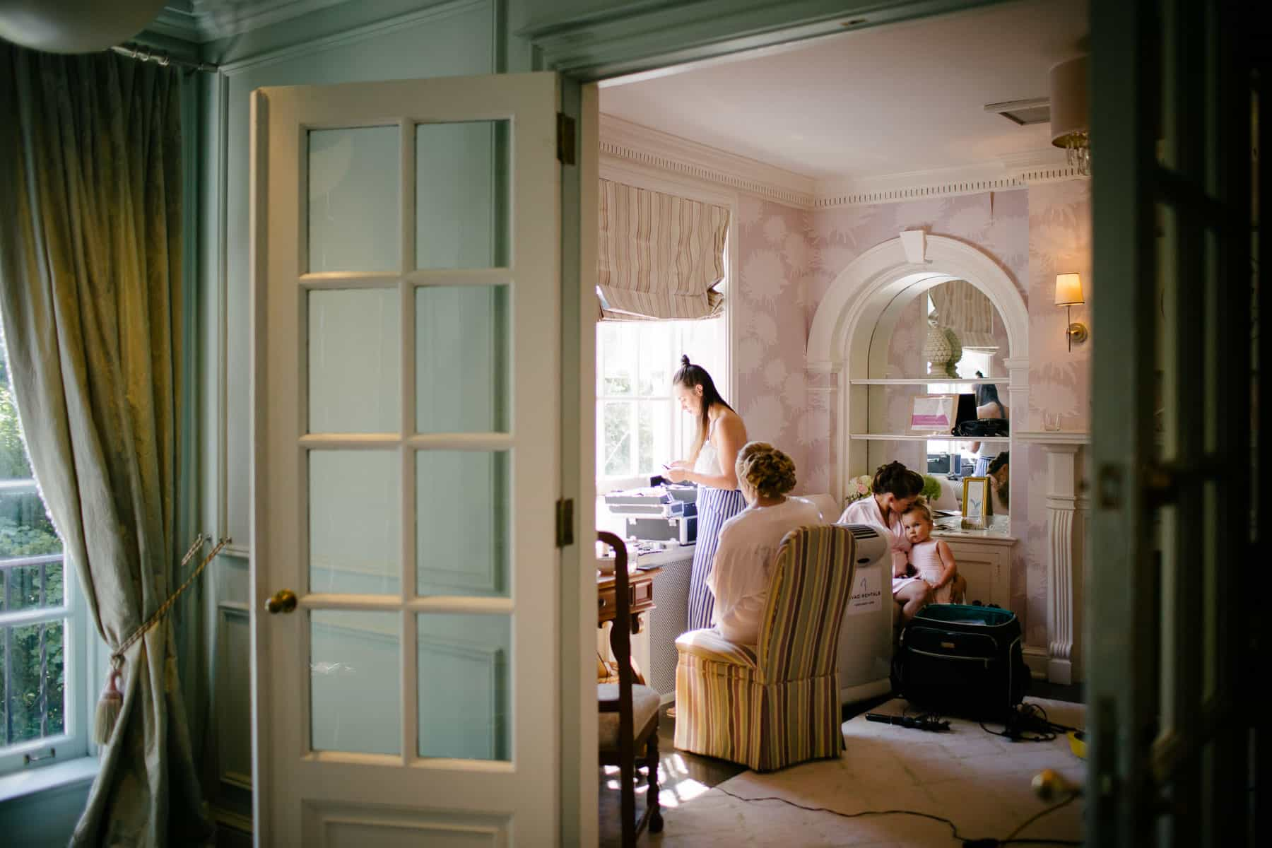 Wide shot of bride getting makeup done in bridal suite of McClain House, Estates of Sunnybrook.
