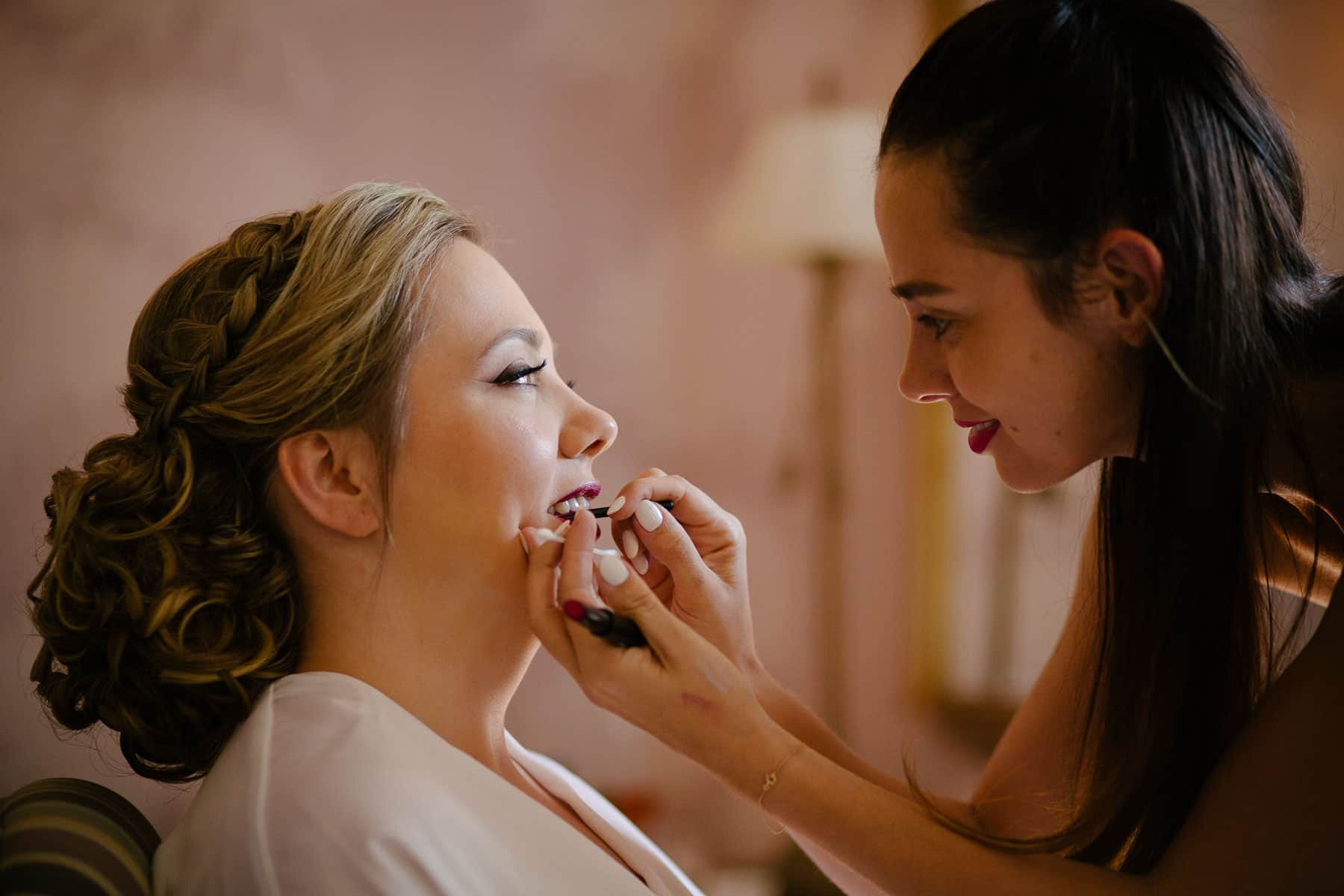 Bride's lipstick applied by makeup artist in bridal suite at McClain House, Estates of Sunnybrook.