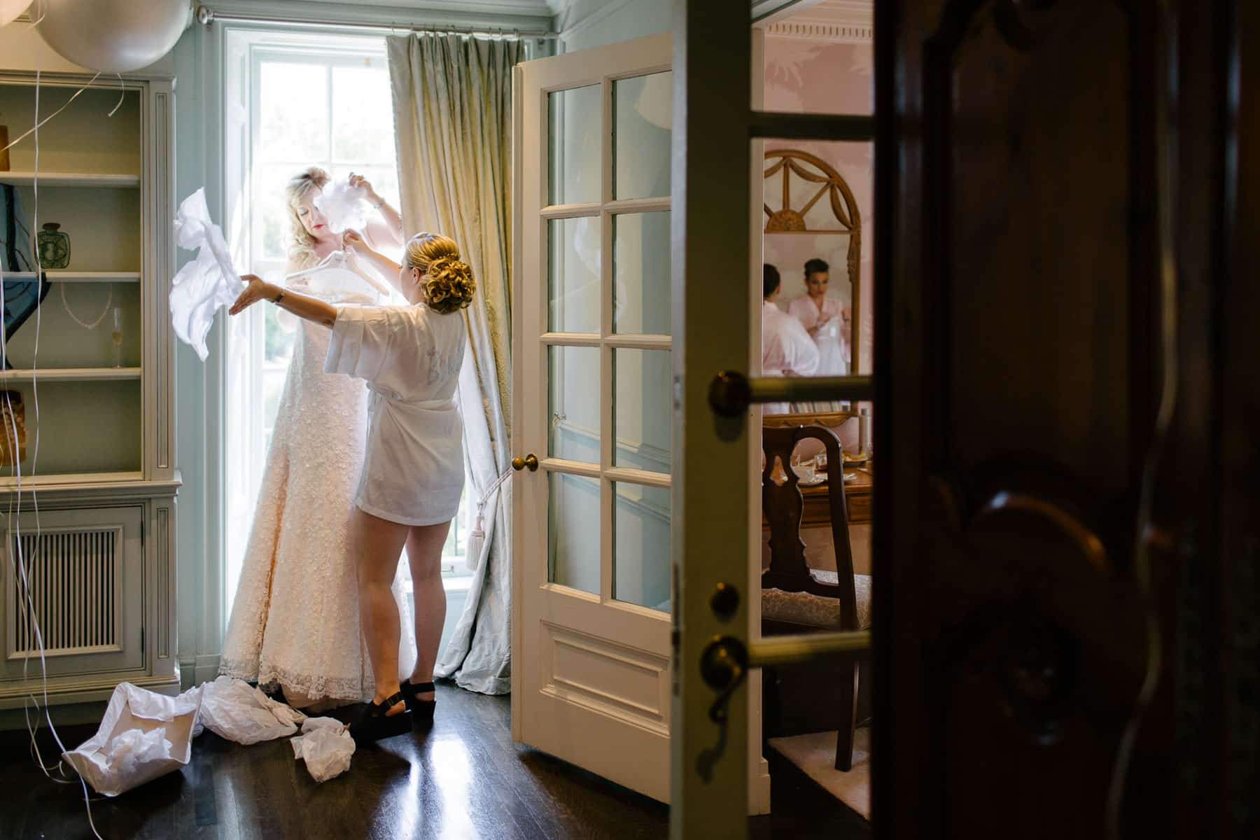 Bride and her mother unpack the wedding dress in bridal suite at McClain House, Estates of Sunnybrook.