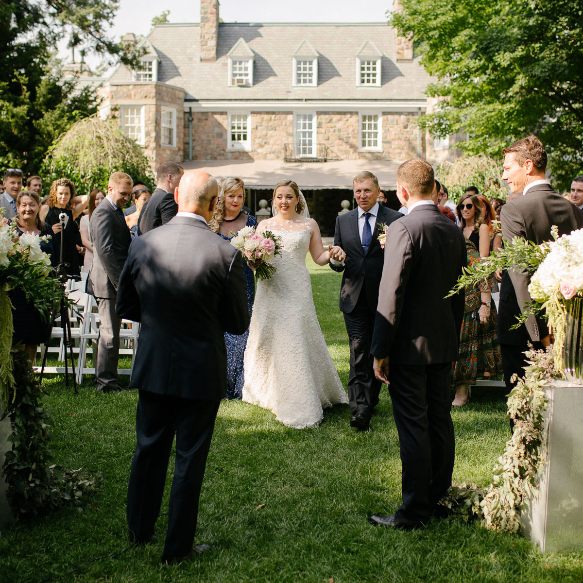 Bride is emotional while walking down aisle with parents towards groom at McClain House, Estates of Sunnybrook.