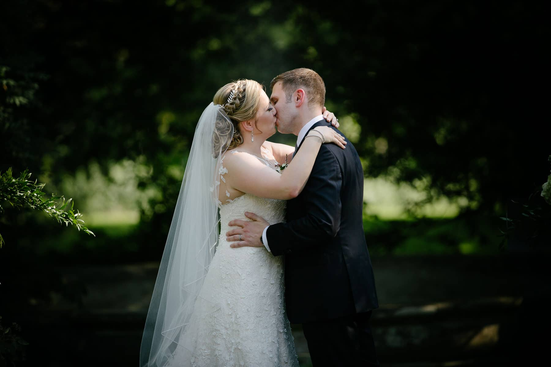 Bride and groom kissing during wedding ceremony at McClain House, Estates of Sunnybrook.