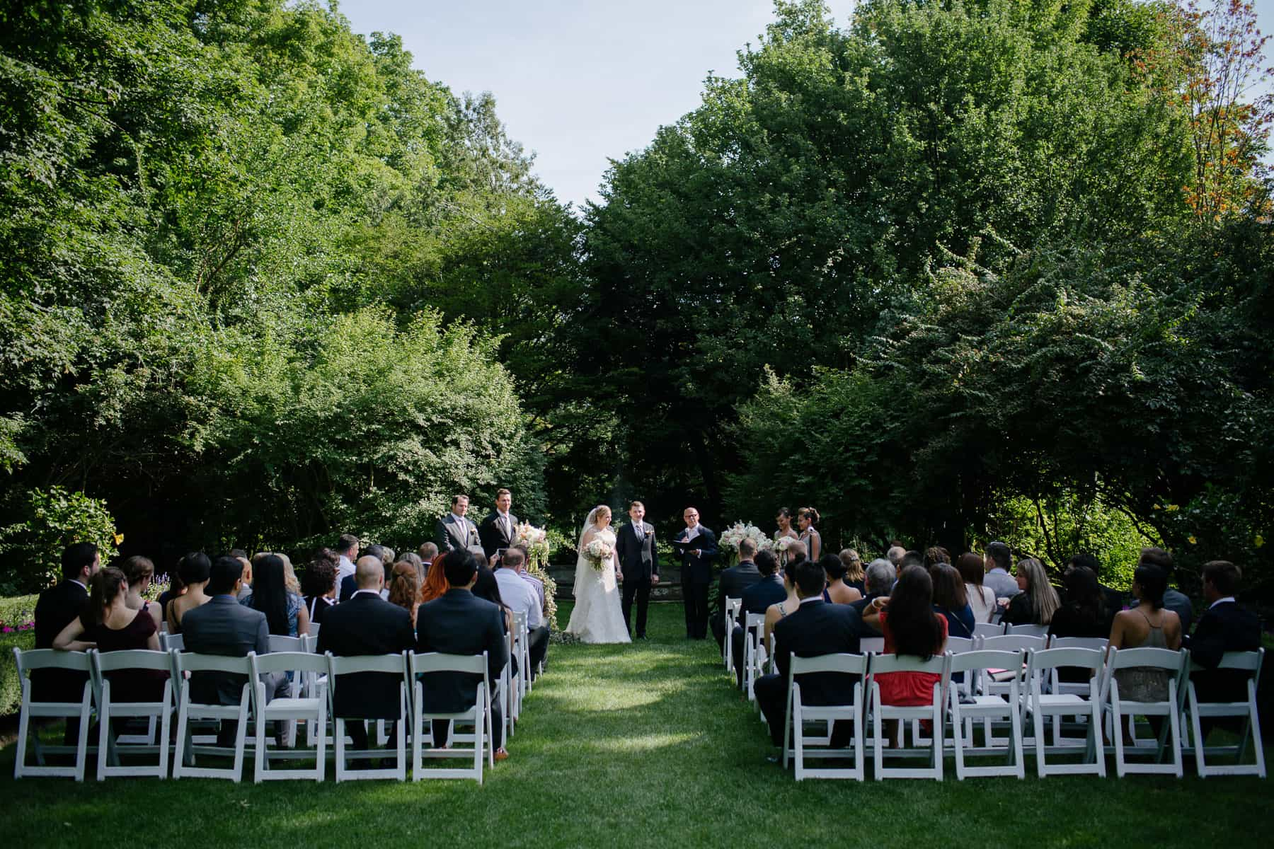 Wide shot of bride and groom and guests during wedding ceremony at McClain House, Estates of Sunnybrook.