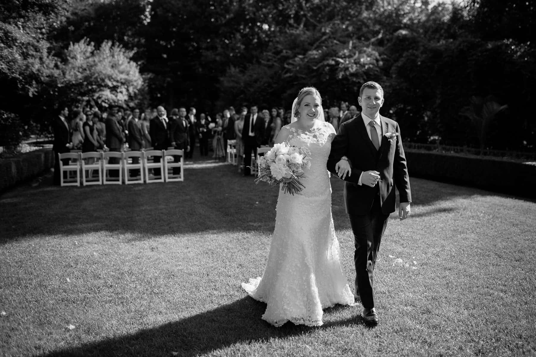 Bride and groom walking past photographer after wedding ceremony at McClain House, Estates of Sunnybrook.