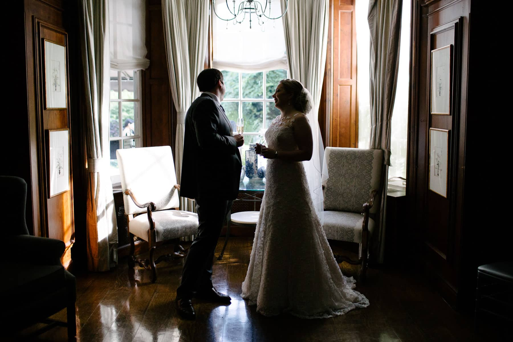 Silhouette of bride with guest in the library room of McClain House, Estates of Sunnybrook.