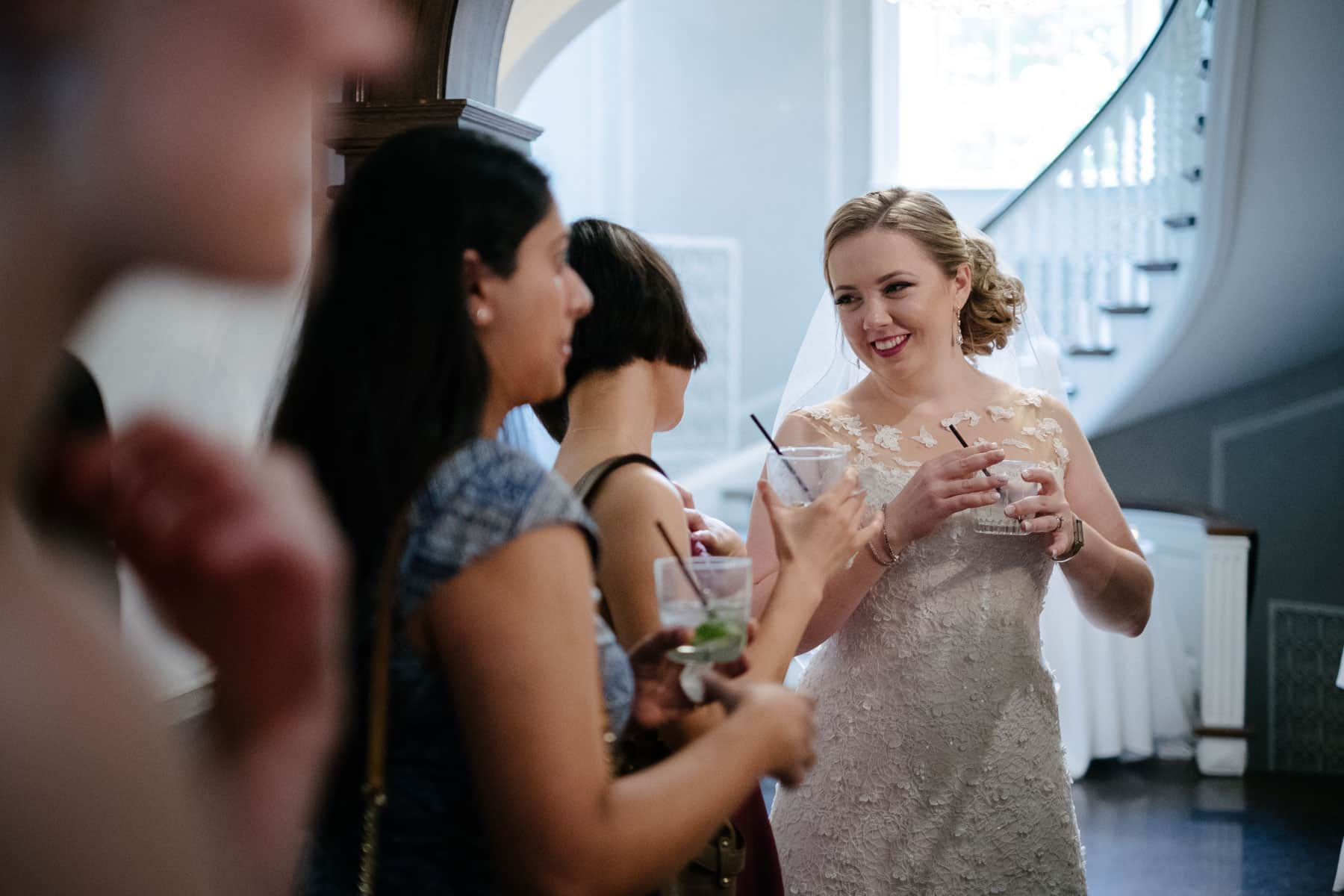 Bride drinking a cocktail and talking with guests at McClain House, Estates of Sunnybrook.