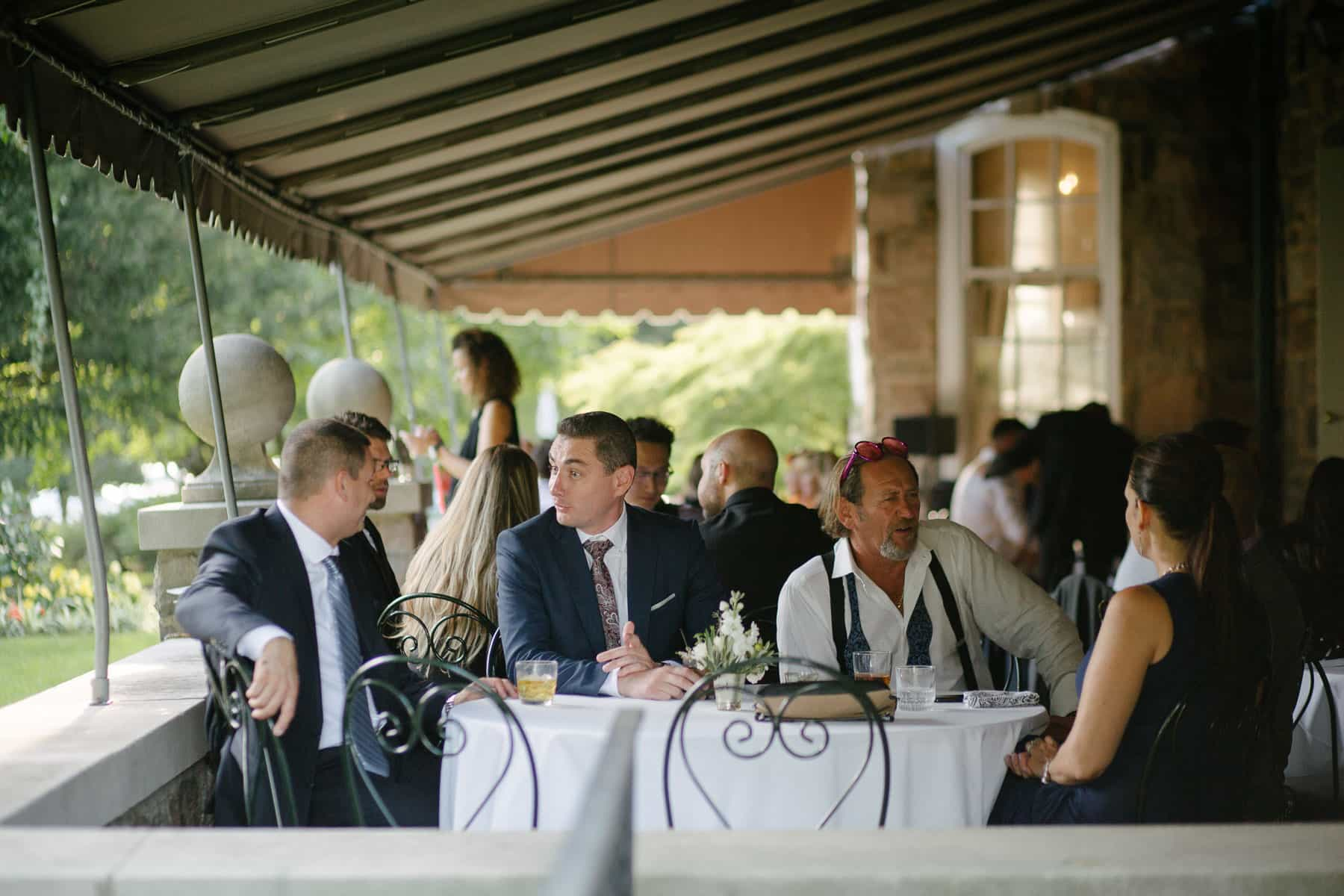 Wedding guests having a conversation around patio table at McClain House, Estates of Sunnybrook.
