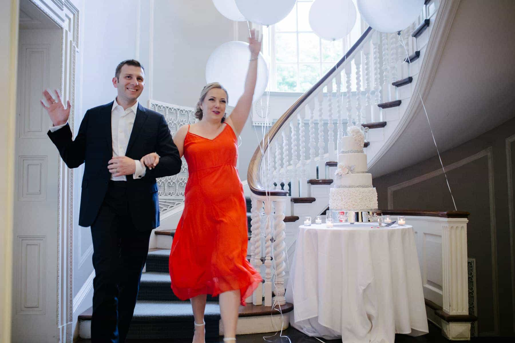 Groom and bride (in red dress) descent stairs at McClain House, Estates of Sunnybrook.