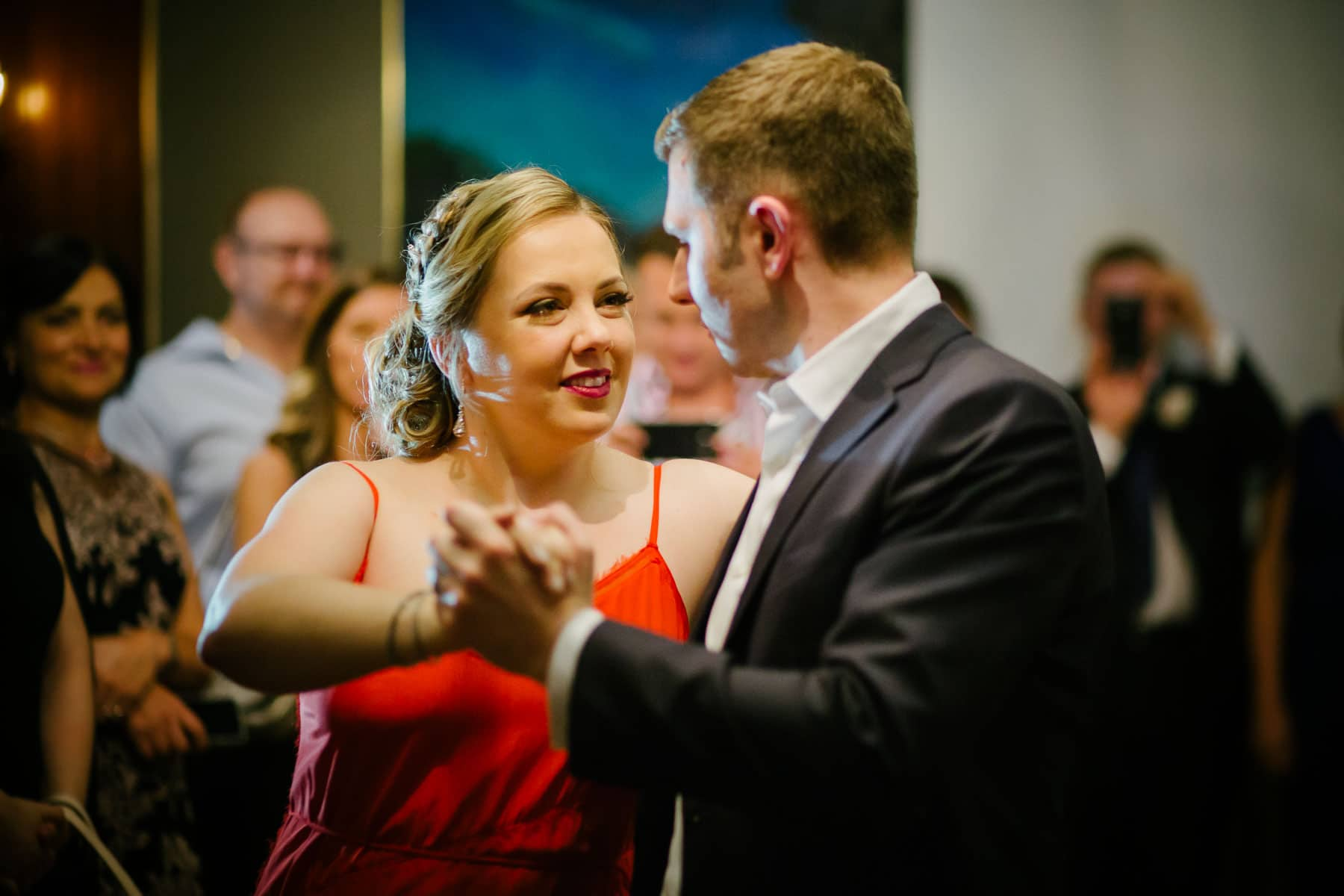 Medium shot of bride and groom dancing tango while guests watch at McClain House, Estates of Sunnybrook.