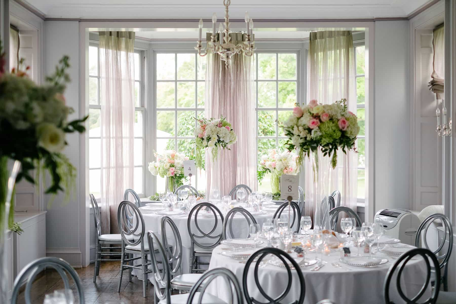 View of dinner reception hall with flowers and tables at McClain House, Estates of Sunnybrook.