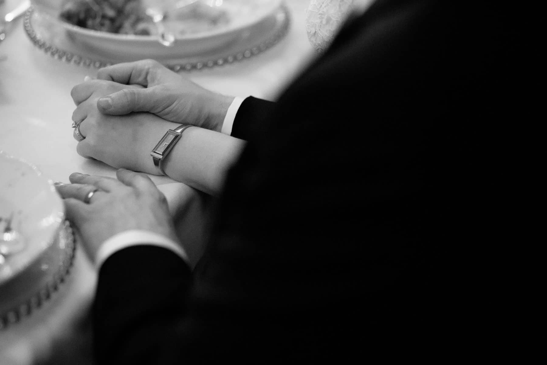 Closeup of bride and groom's hands during reception at McClain House, Estates of Sunnybrook.