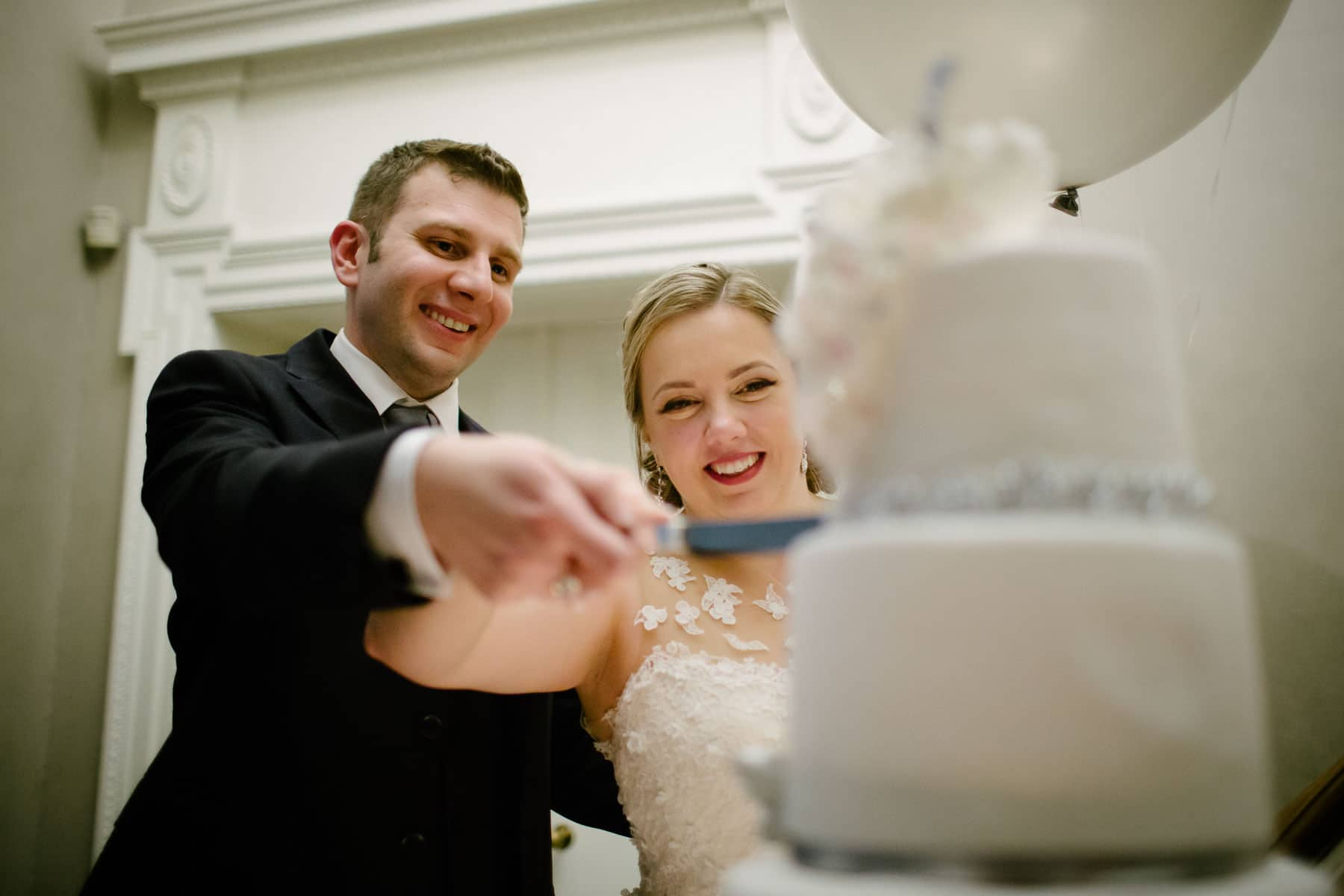Bride and groom smiling and cut the wedding cake at McClain House, Estates of Sunnybrook.