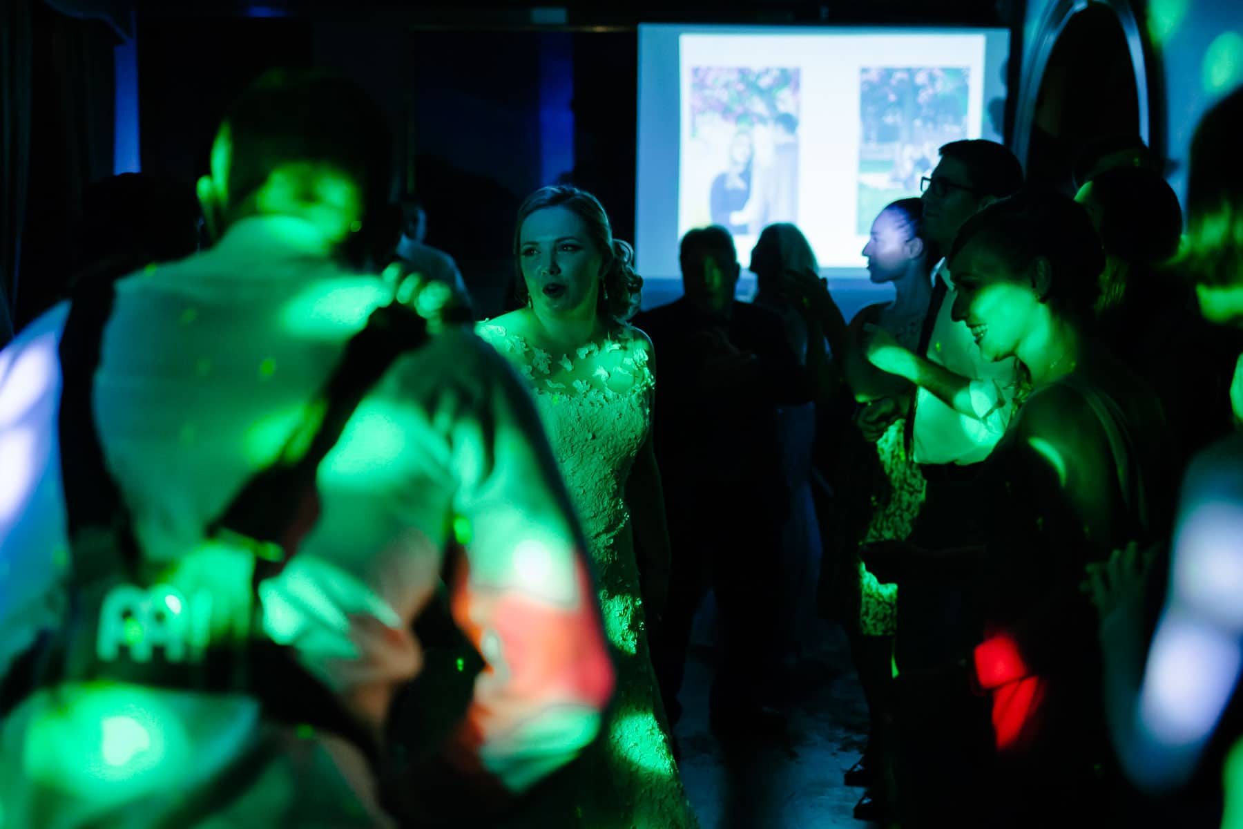 Bride dancing with guests in green light in the McClain House, Estates of Sunnybrook.