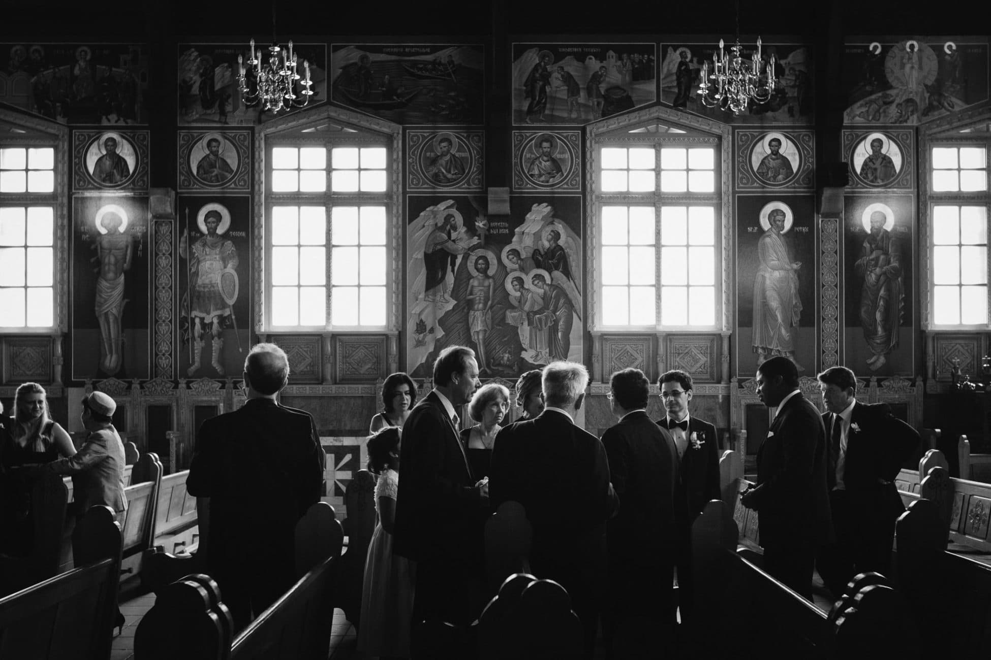 The groom and best man with guests inside Saint George Romanian Orthodox Church of Toronto.