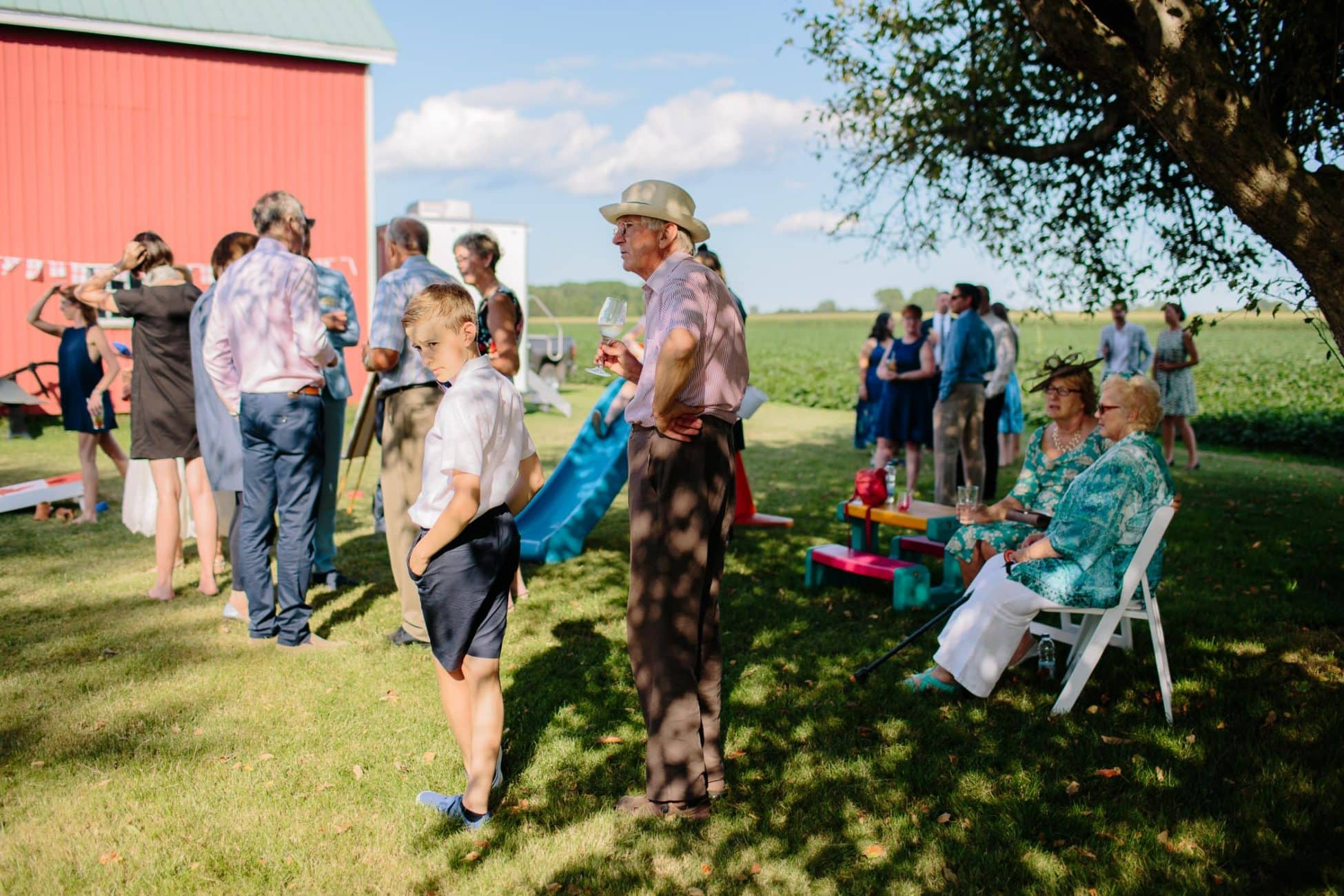 A dozen wedding guests and a young boy standing under a tree in mottled shade during the cocktail reception at a family farm wedding in rural Ontario.