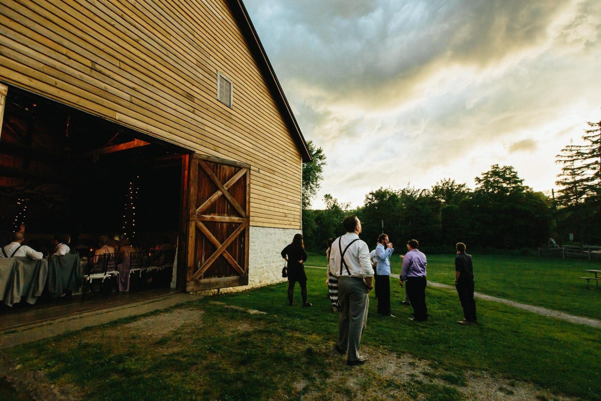 The guests looking at dramatic stormy clouds before sunset outside barn at Ball's Falls in this documentary wedding photograph.