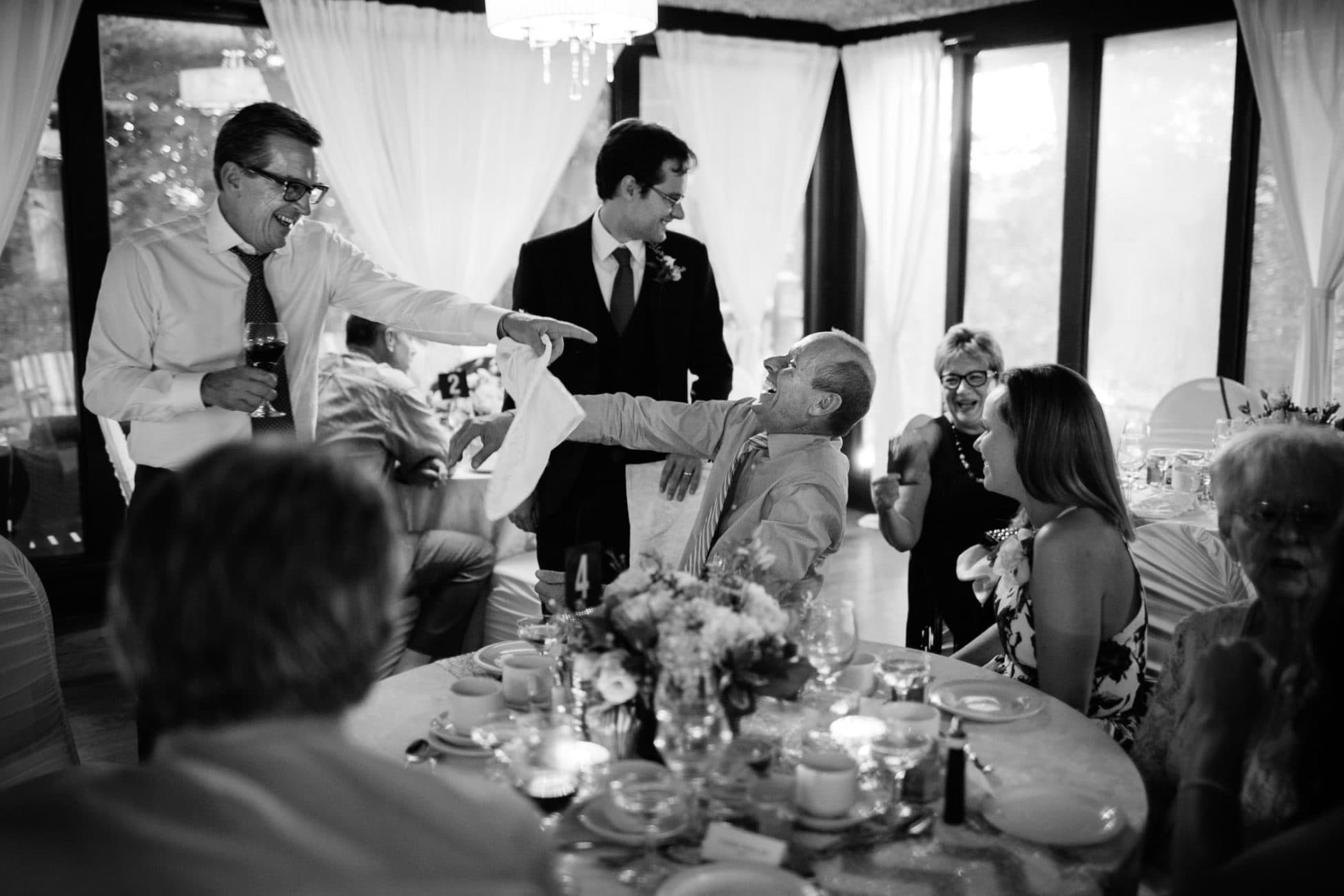 Two guests pointing and laughing at each other during wedding reception at Fantasy Farm in Toronto wedding photography by Pavel Kounine.