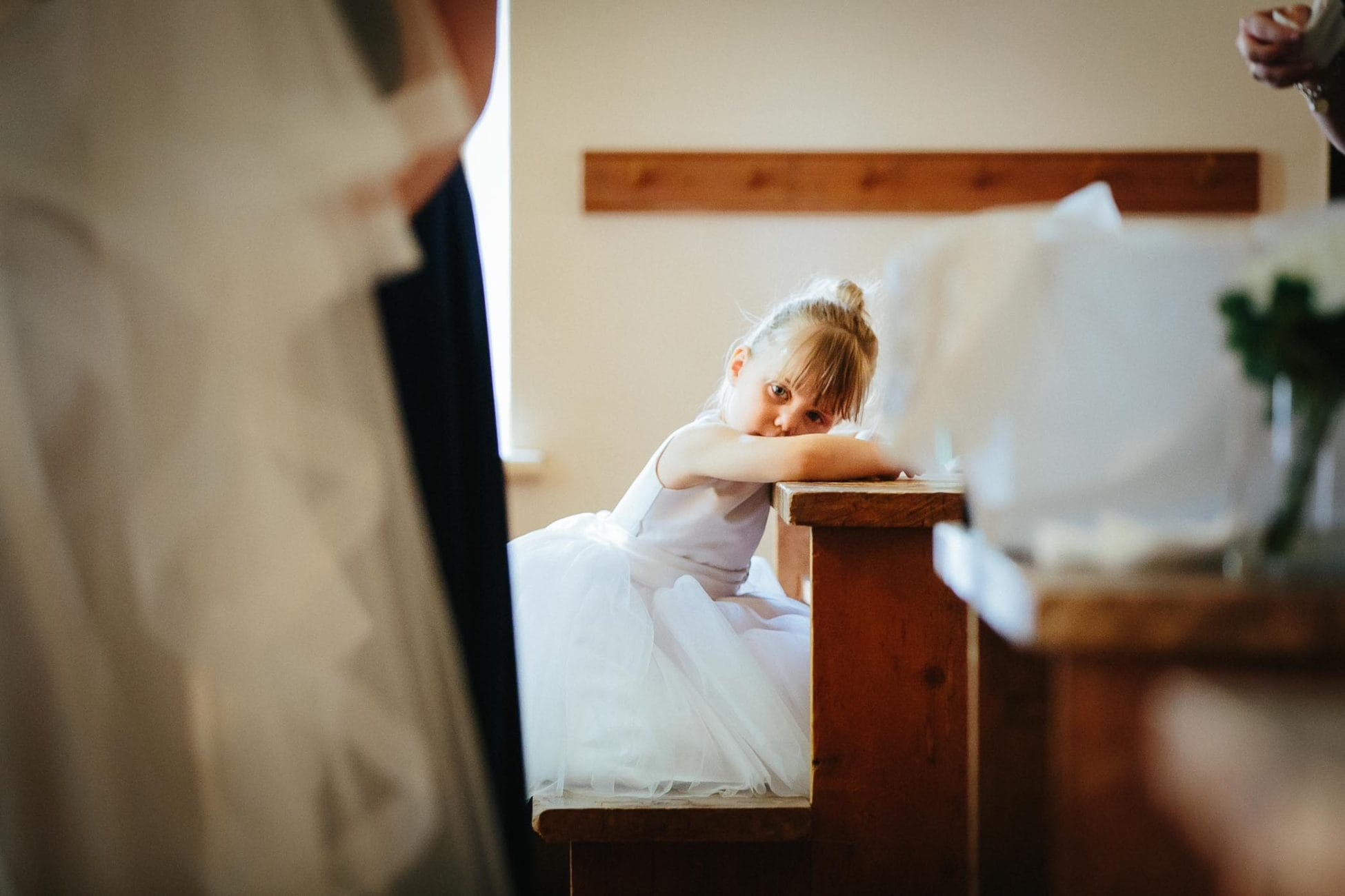 The flower girl in a white dress leaning on desk looking at Toronto wedding photographer Pavel Kounine at this Enoch Turner Schoolhouse wedding ceremony.
