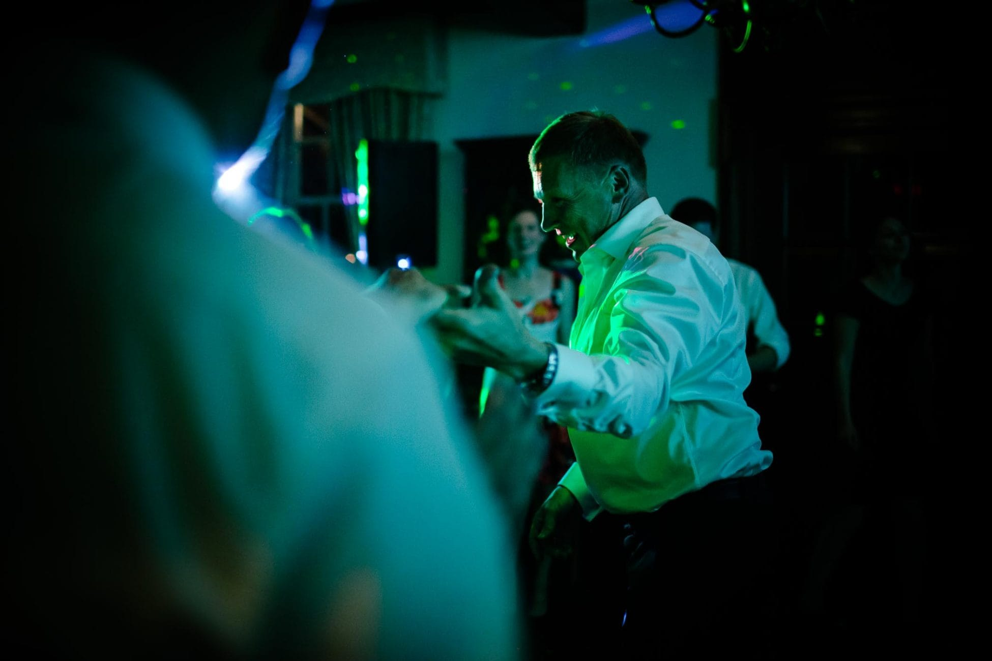 A man dancing to DJ music with green light and lasers at this McLean House at Estates of Sunnybrook wedding in Toronto. Documentary wedding photography by Pavel Kounine.