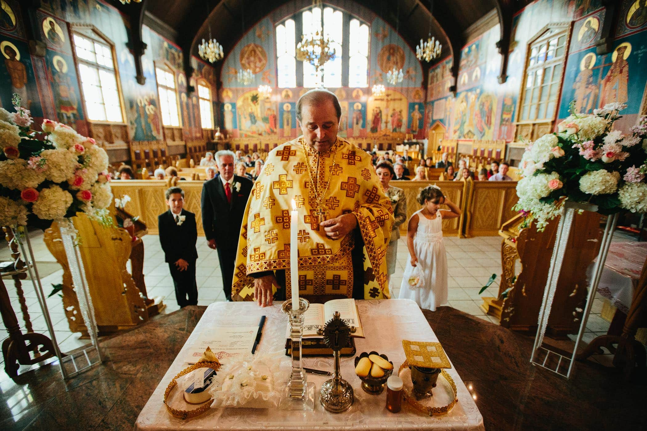 The priest with hand on altar inside saint george romanian orthodox church wedding ceremony by photojournalistic wedding photographer Pavel Kounine