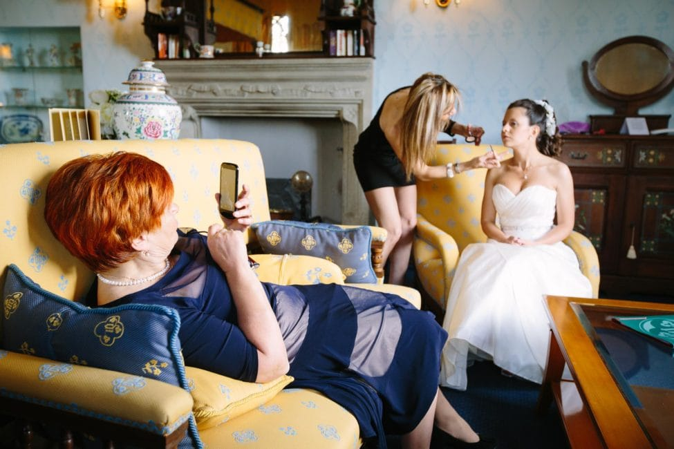 The bride getting makeup done while her mother leans back in sofa to take photo. Wedding photojournalism inside the Castello Dal Pozzo on Lake Maggiore in Italy.