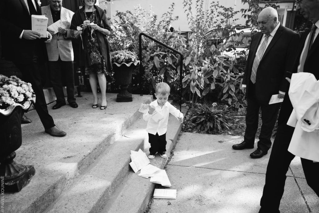 Wedding photography ceremony, little boy usher drops the wedding programs.