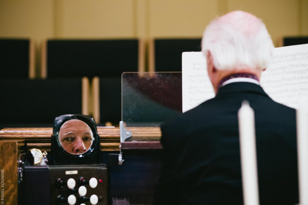 Photojournalistic wedding photography ceremony, reflection of organ player.