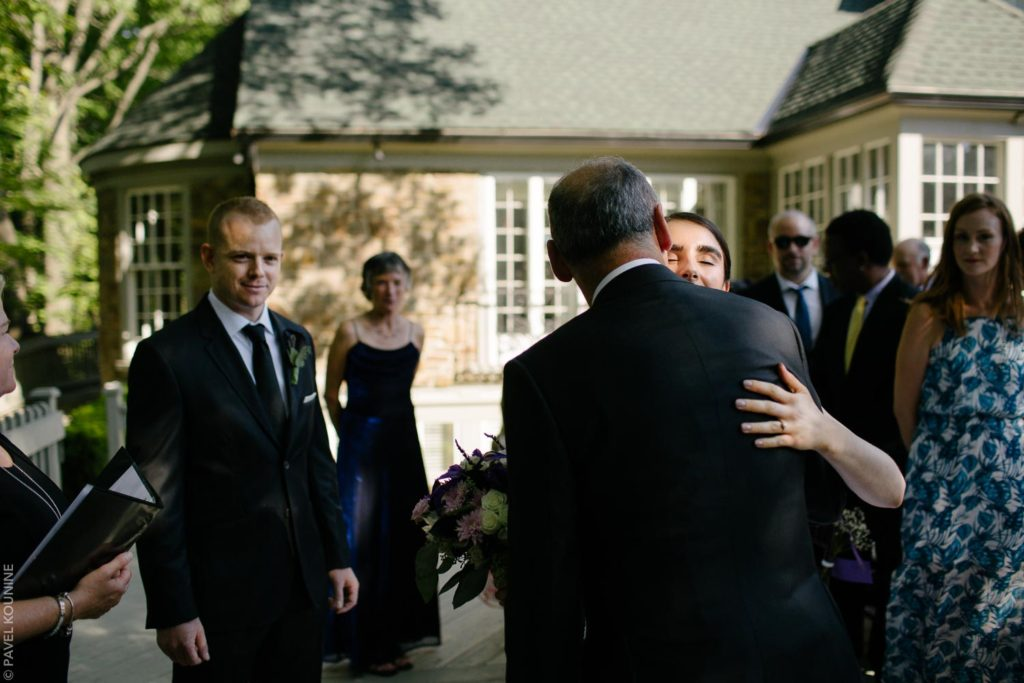 Wedding photography ceremony, bride hugs father.