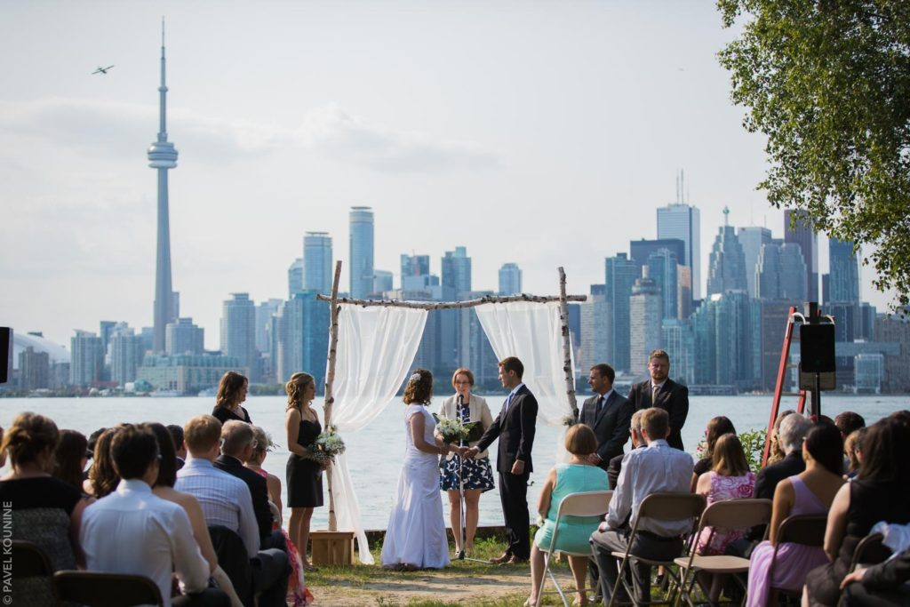 Photojournalistic wedding photography ceremony, bride and groom and wedding party during the ceremony on Toronto island with Toronto skyline.