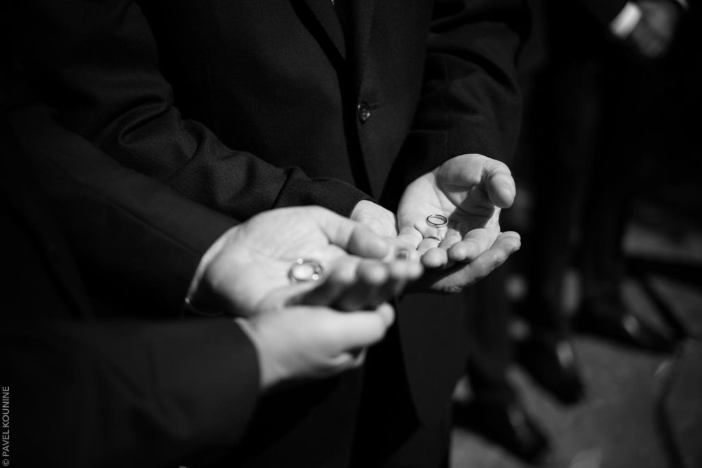 Photojournalistic wedding photography ceremony, pages hold present wedding bands in hands.
