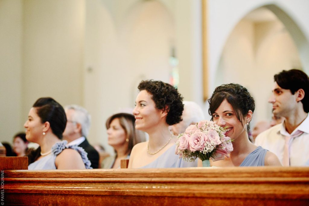 Photojournalistic wedding photography ceremony, bridesmaids smiles at photographer.