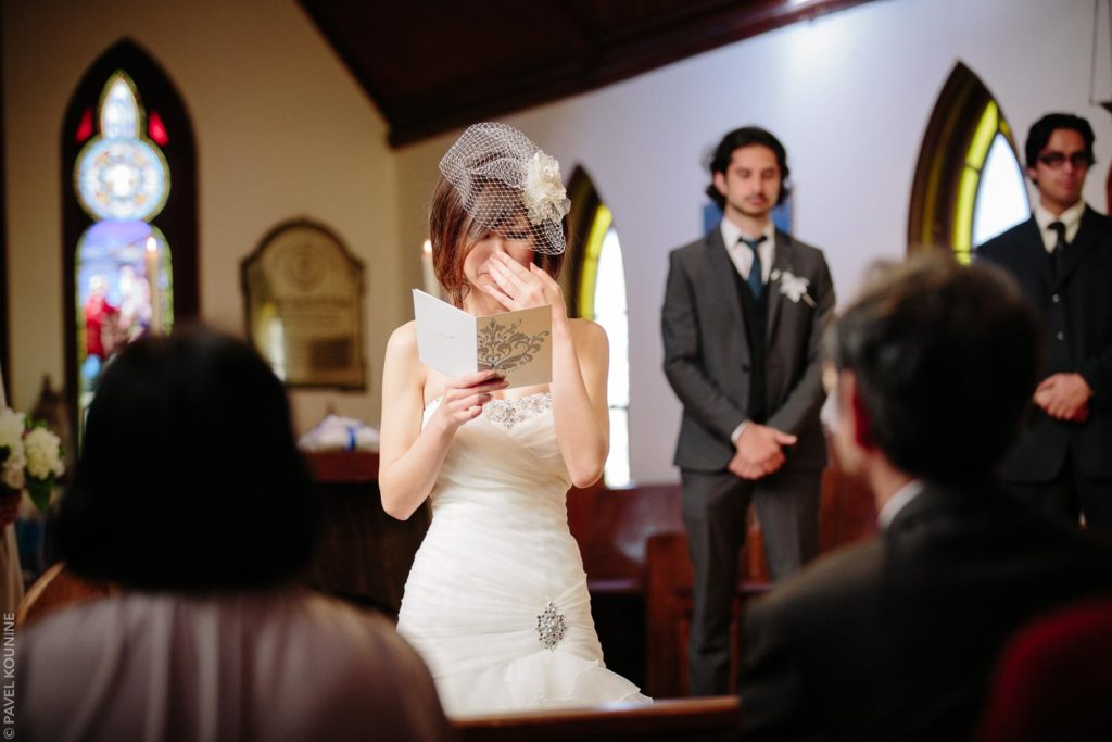 Photojournalistic wedding photography ceremony, bride cries as she reads from a card.