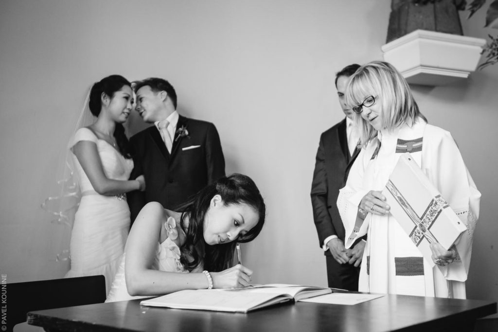 Photojournalistic wedding photography ceremony, bride and groom whisper as maid of honour signs marriage register.