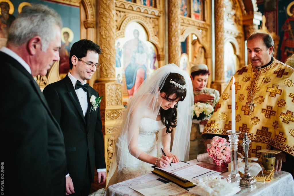 Photojournalistic wedding photography ceremony, bride signs the marriage register.