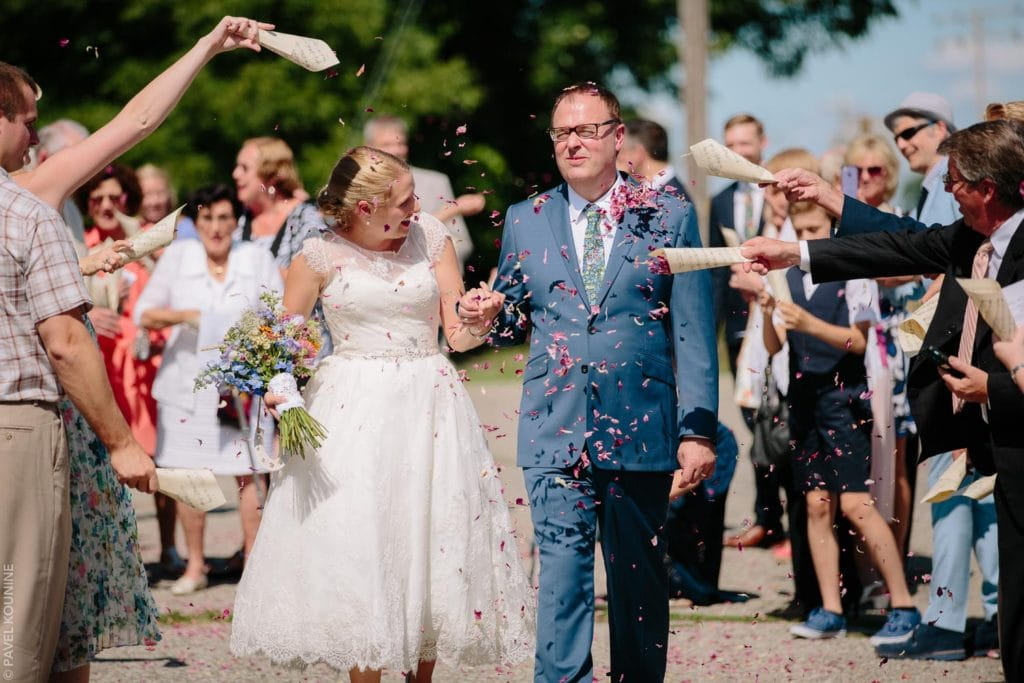 Wedding photography ceremony, flower petal confetti thrown at bride and groom by guests.