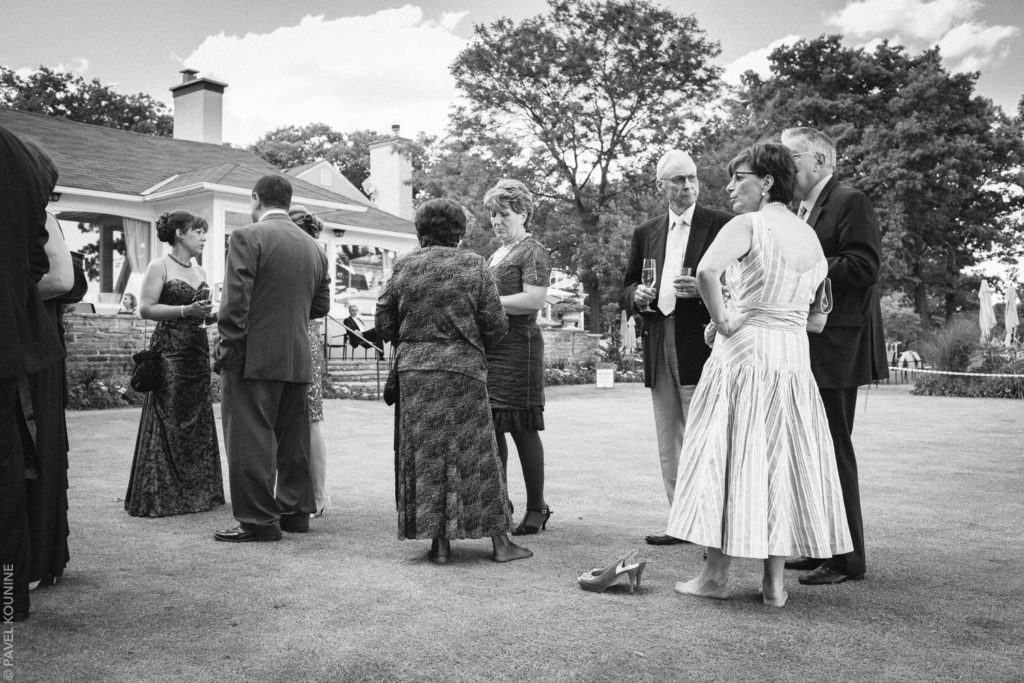 Wedding photography cocktail hour, a barefoot woman and other guests on a manicured lawn of a country club.
