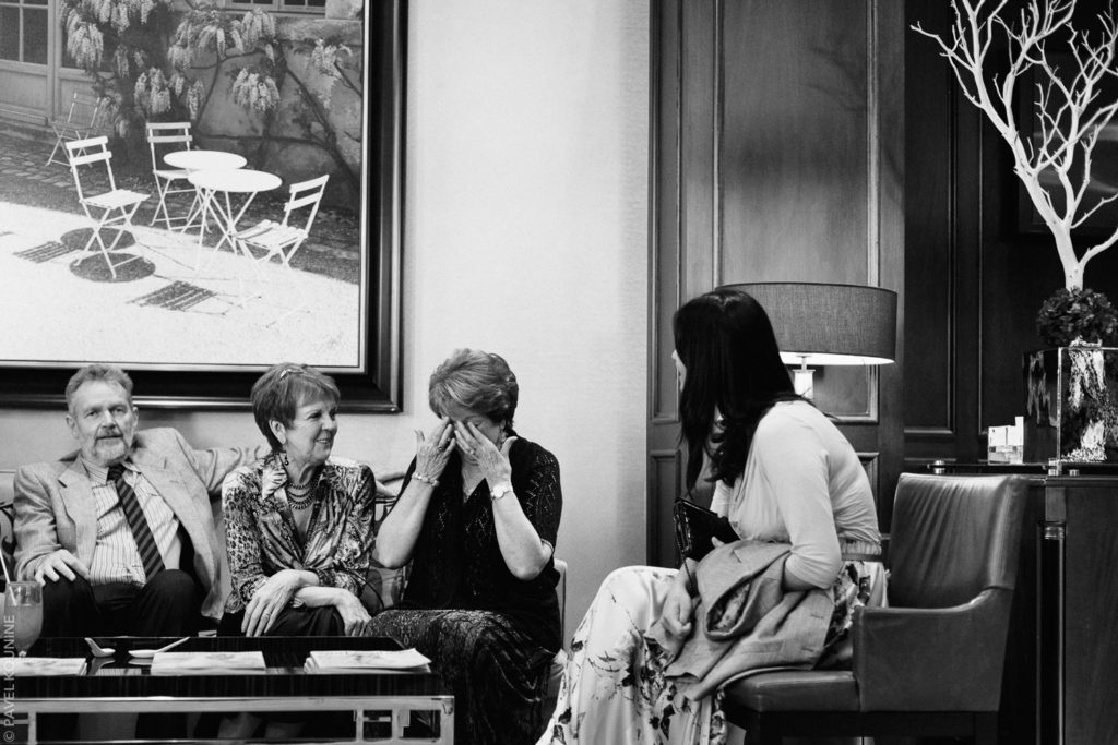 Photojournalistic wedding photography cocktail hour, an older woman cries sitting with guests.