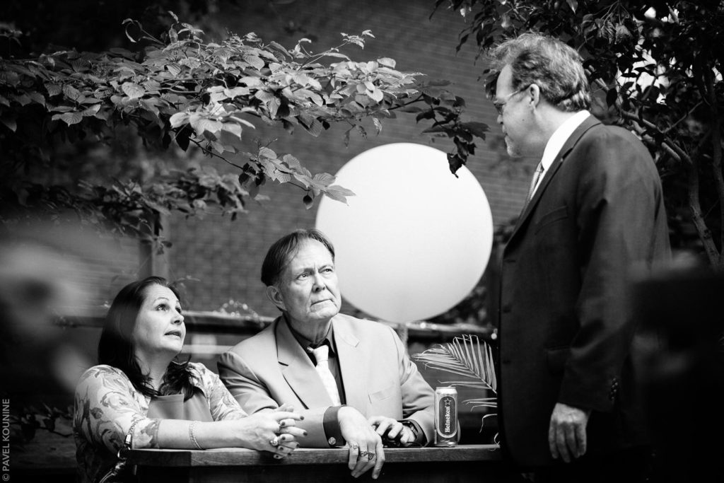 Three guests talking during cocktail hour in backyard wedding in Toronto.
