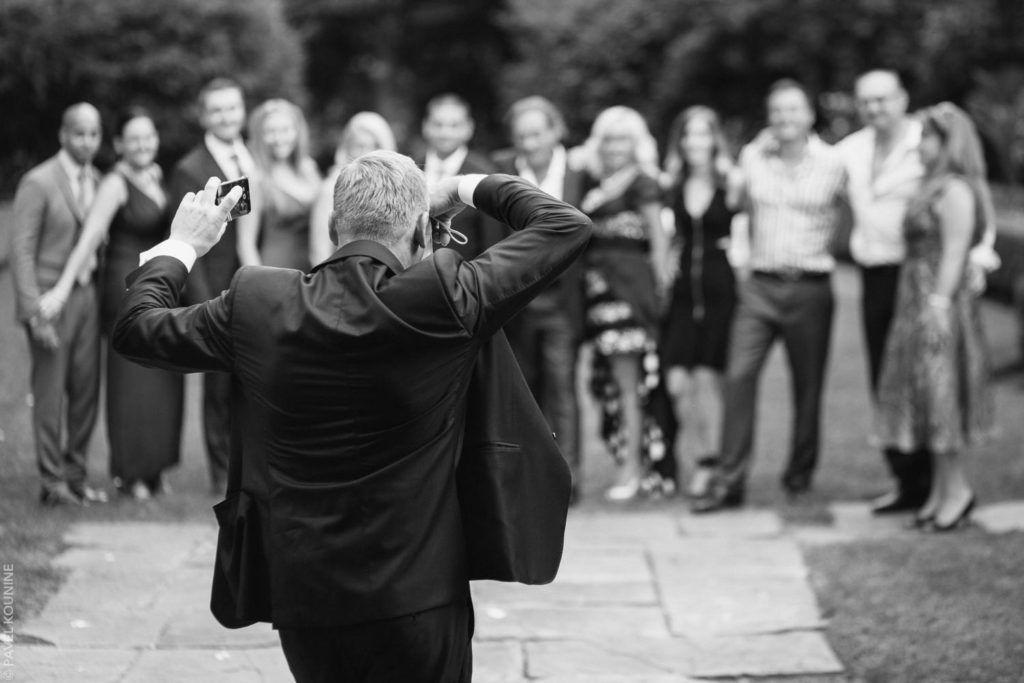 Man with cameras in each hand taking photos of guests during cocktail hour.