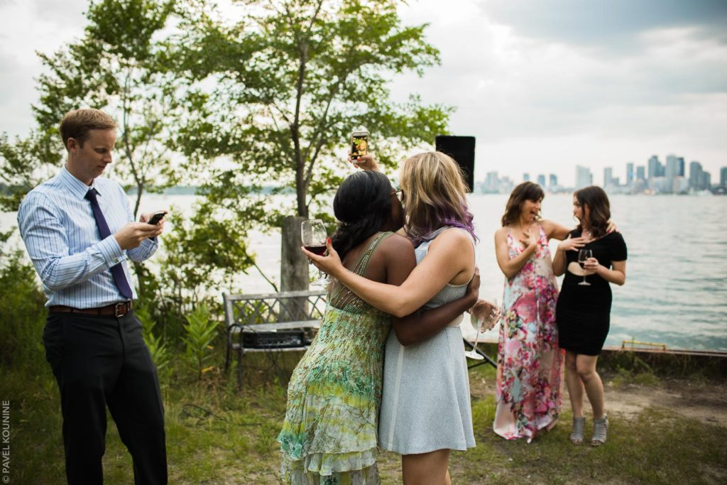 Two female guests hug for selfie at Toronto island wedding cocktail hour.