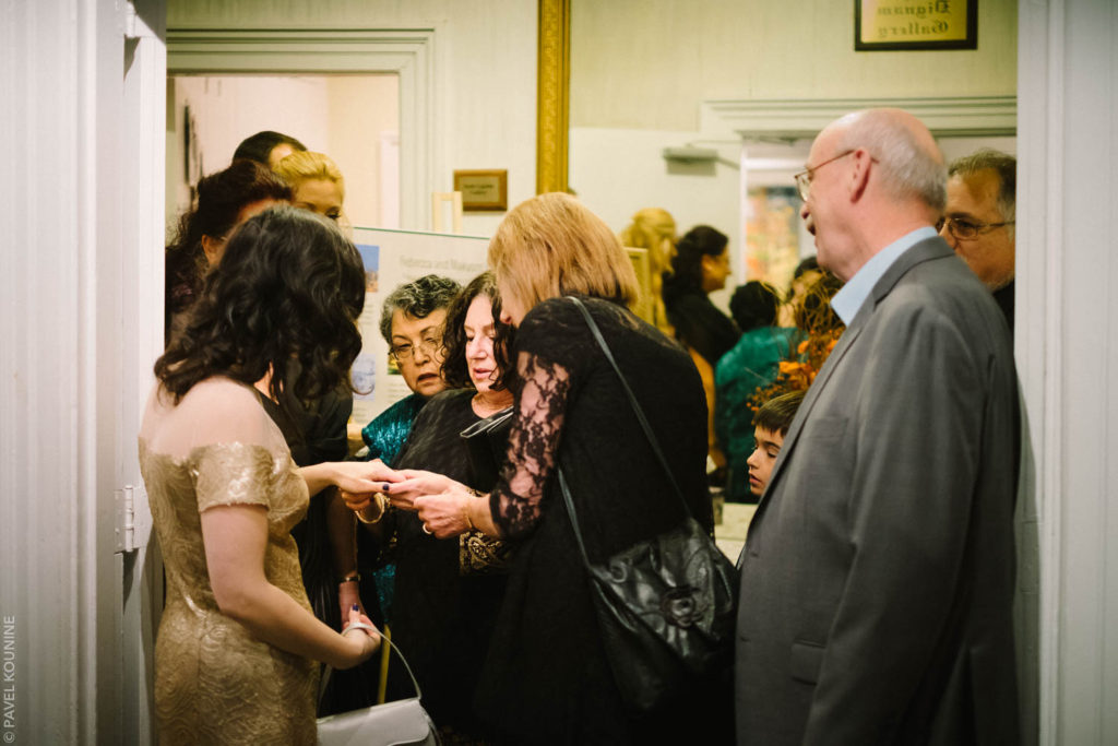 Several older women examine the bride's engagement ring after the wedding ceremony.