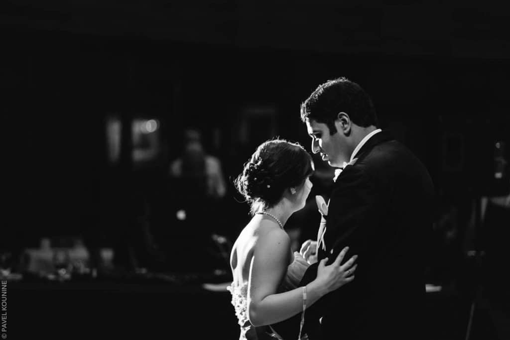Photojournalistic wedding photography first dance, bride and groom in silhouette.
